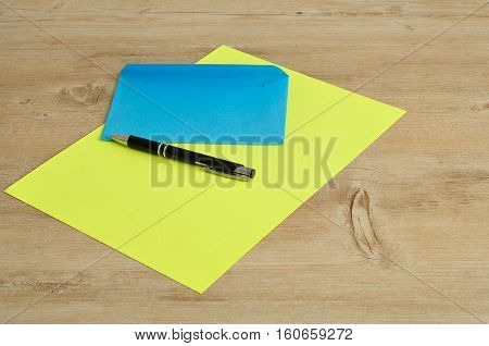 A yellow paper and a blue envelope with a black pen