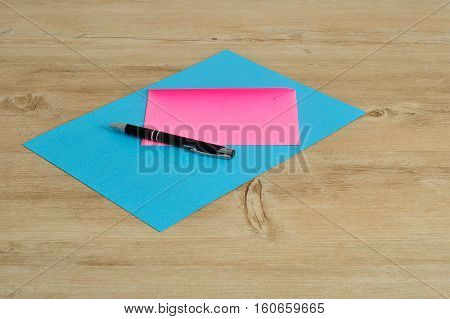 A blue paper and an a pink envelope with a black pen