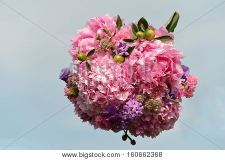 A Bridal Bouquet of English Country Flowers against the Sky