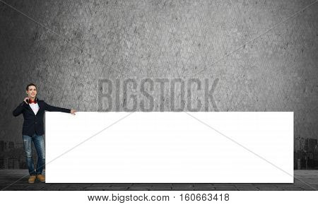 Handsome guy wearing headphones and holding white blank banner