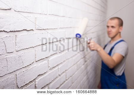 Young Handsome Man Painter In Uniform Painting Brick Wall With Paint Roller