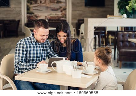 family, parenthood, technology and people concept - happy mother, father and little girl with tablet pc computer having dinner at restaurant.