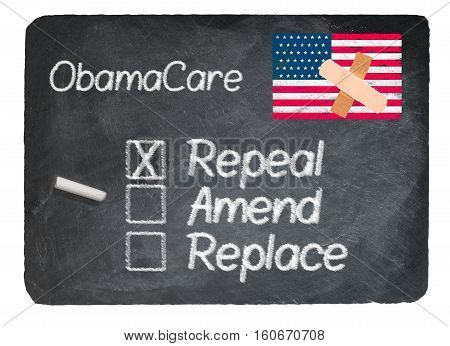 Obamacare health plan choice for repeal written in chalk on a chalky natural slate blackboard isolated against white background