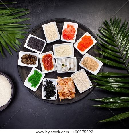 Ingredients for sushi on black plate in dark wooden background