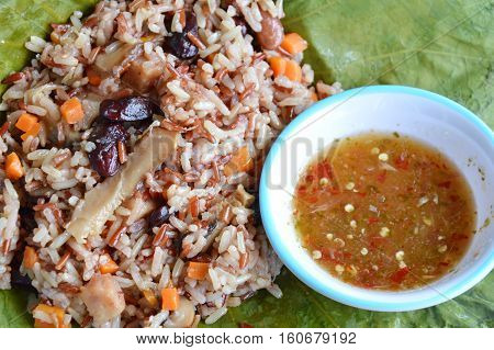 steamed rice and whole grain wrapped in lotus leaf with spicy sauce
