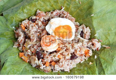 shrimp and salt egg topping on steamed rice wrapped in lotus leaf