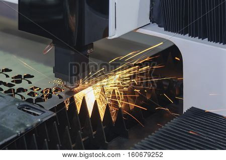 The laser cutter machine while cutting the sheet metal with the sparking light