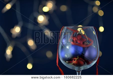Glass wine glass with Christmas toys on bokeh background.