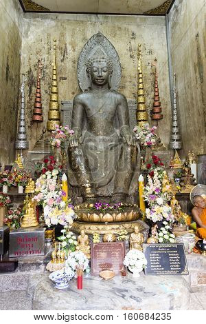 AYUTTHAYA, THAILAND - November 4, 2016: Statue of a Buddha carved from black stone in the European posture seated in a chair with hands on the knees and both feet on the ground in Ayutthaya Thailand