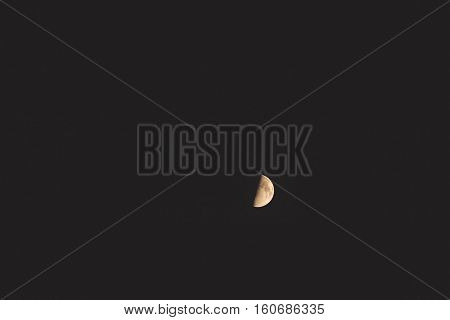 View of the moon about half full against black sky background.