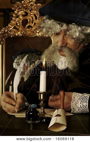 Historically dressed man writing his will (or a letter) with a goose feather - lighting is Rembrand style,