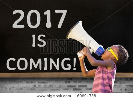 Boy with megaphone against 2017 new year sign on blackboard