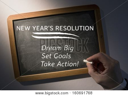 Hand writing new year resolution goals on slate board