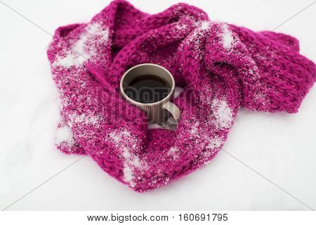 season, drinks, christmas and winter holidays concept - tea or coffee mug and knitted woolen scarf on snow