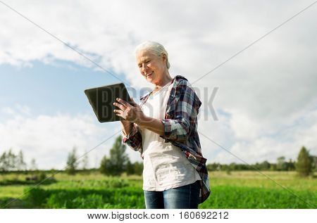 farming, agriculture, technology, old age and people concept - happy senior woman with tablet pc computer at county or farm