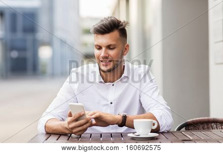 business, technology and people concept - happy young man with smartphone and coffee cup texting at city street cafe