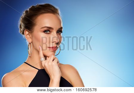 people, luxury, jewelry and fashion concept - beautiful woman in black wearing golden earrings and ring with diamonds over blue background