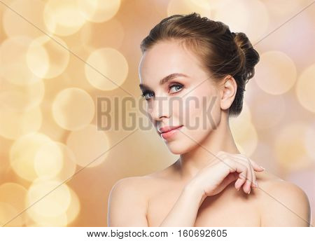 beauty, people and health concept - beautiful young woman face over holidays lights background