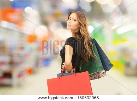 sale and people - woman with colorful shopping bags over supermarket background