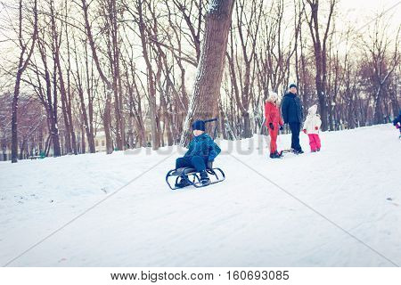 happy family with child on sled walking in winter outdoors