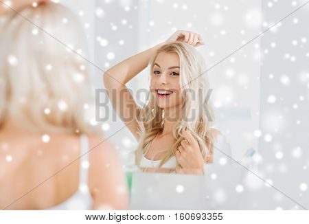 beauty, hygiene, hairstyle, morning and people concept - smiling young woman looking to mirror at home bathroom over snow