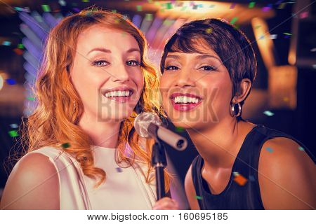 Female friends singing together in bar against flying colours