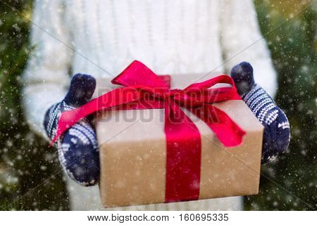 close-up of nicely wrapped christmas present being held by somebody in mittens cozy and snowing holiday concept