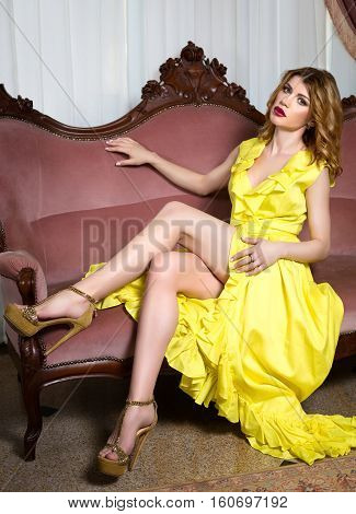 Elegant young woman in evening dress posing in interior. Fashion style portrait of a beautiful girl in interior.