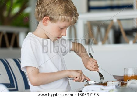 little serious boy eating breakfast with fork and knife at hotel or resort
