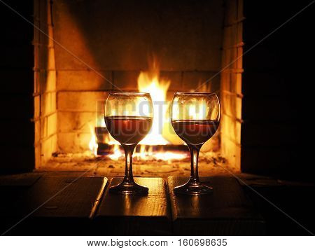 Two glasses of wine on the background of a burning fireplace. Concept winter evening together heat in the house holiday