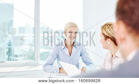 Businesswoman listening to offers of colleague at meeting