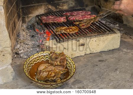 roasting fresh meat in the fireplace and bowl with steak . Make BBQ