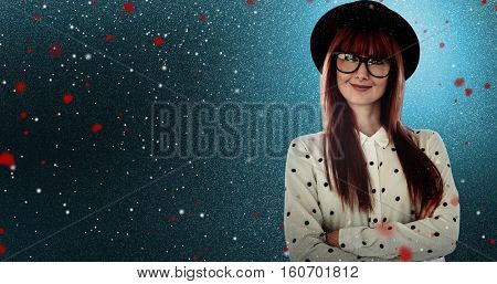 Portrait of a smiling hipster woman with arms crossed against snow