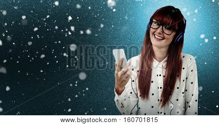 Attractive hipster woman listening to music with headphones against snow