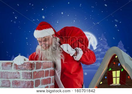 Santa Claus carrying bag full of gifts looking in chimney against winter snow scene