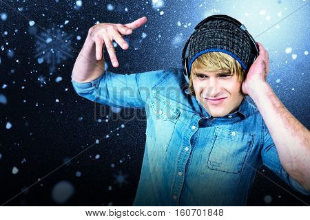 Cheerful hipster listening to music against snow with red flakes
