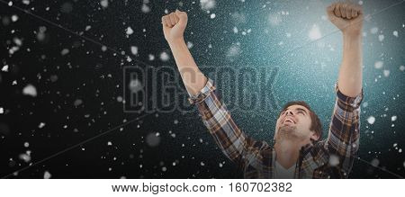 Hipster with laptop on lap cheering with arms raised against snow