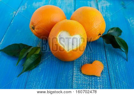 A few ripe oranges with leaves on a blue wooden background. One cut orange peel in the shape of a heart.