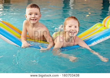 Portrait of two little children swimming in pool raft
