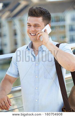 Young Man Talking On Mobile Phone Walking To Work