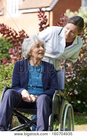 Female Carer Pushing Senior Woman In Wheelchair