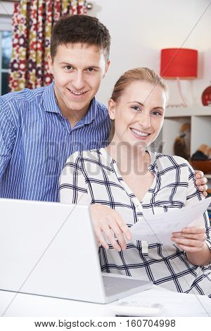 Portrait Of Couple Discussing Domestic Finances At Home