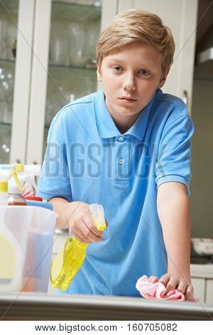 Portrait Of Unhappy Boy Helping to Clean House