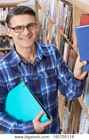 Portrait Of Mature Male Student Studying In Library