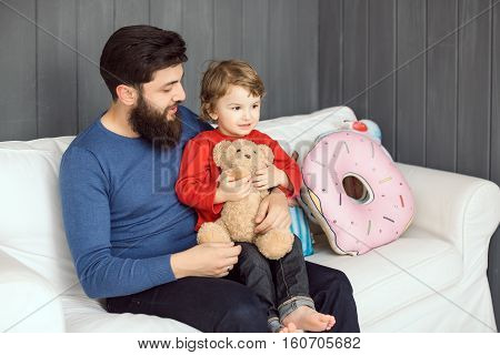 Happy family. Father and son with toy bear playing together at home on sofa