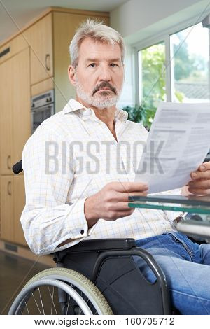 Portrait Of Frustrated Man In Wheelchair Reading Letter