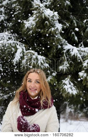 A smiling cheerful girl in in a white sweater and a purple skirt plays with snow outdoors walks on a winter day in the park.