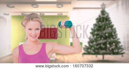 Happy blonde lifting dumbbell and flexing against home with christmas tree
