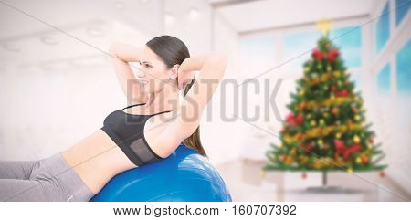 Side view of a fit woman stretching on fitness ball against home with christmas tree