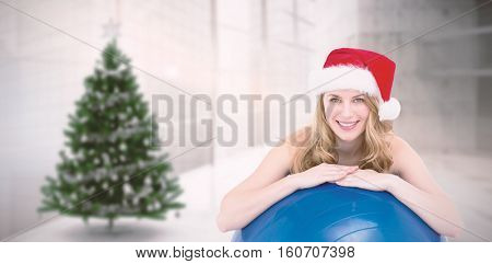 Festive fit blonde leaning on exercise ball against home with christmas tree